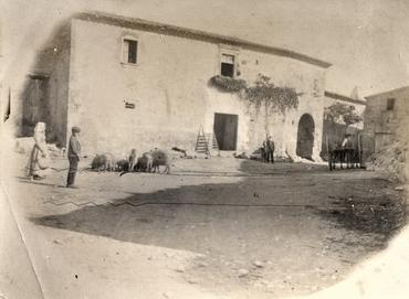 Imatge 51896 - Vista de l'exterior d'una masia amb pagesos i animals