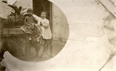 Imatge 51904 - Retrat de nens amb un cavall de fusta al pati d'una casa