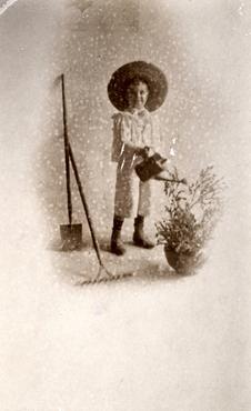 Imatge 51905 - Retrat d'un nen regant un test amb flors