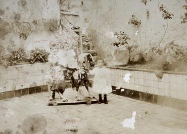 Imatge 51936 - Retrat de tres nens jugant amb un cavall de fusta al pati d'una casa