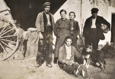 Imatge 51939 - Retrat de grup de cinc pagesos amb un gos davant una masia