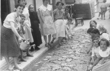 Imatge 54850 - Dones i nens realitzant una catifa de flors al carrer dels Valls de Banyoles