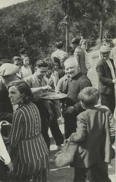 Imatge 54910 - Rector passant el plat de les almoines a l'aire lliure a uns feligresos